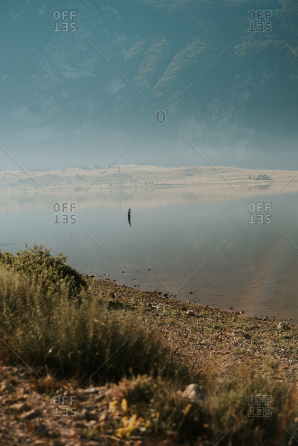 Scenic view of mountain lake with person standing in the shallow water