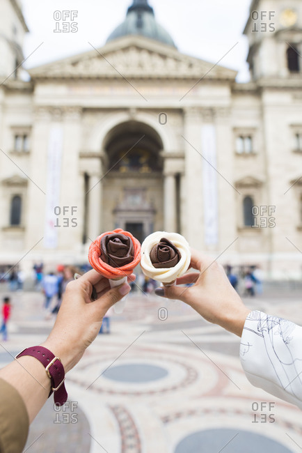 Two people holding chocolate ice cream cones shaped like roses