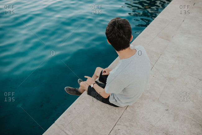 Person sitting at the edge of a pool