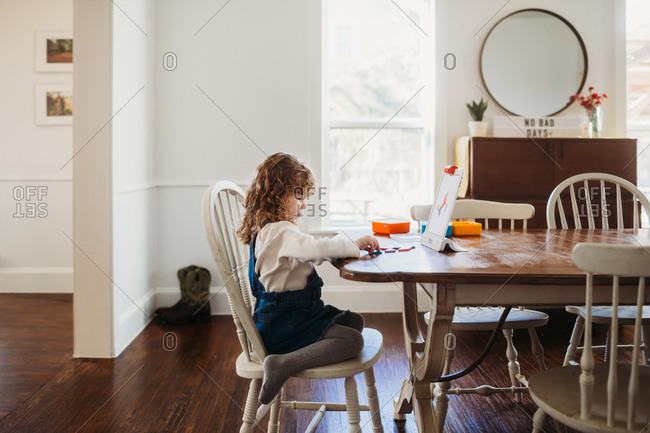 Little girl doing a puzzle with shapes and a tablet on a table