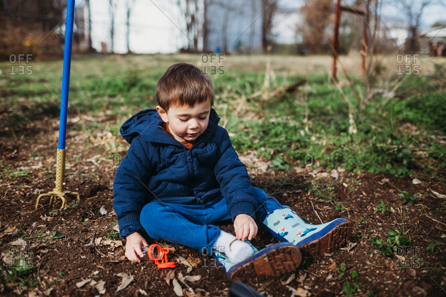 Toddler boy looking for bugs in the dirt