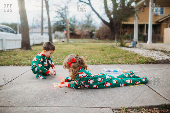 Two kids drawing on sidewalk with chalk in Santa pajamas