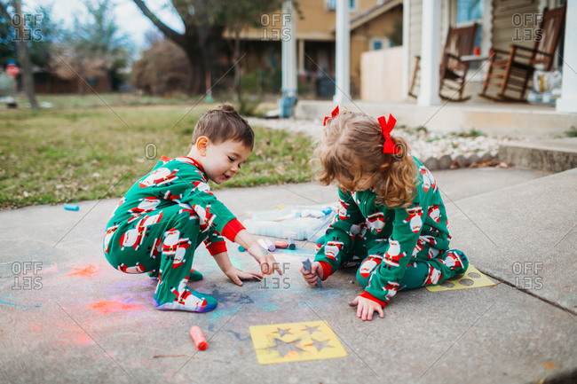 Young siblings drawing on sidewalk with chalk in Santa pajamas
