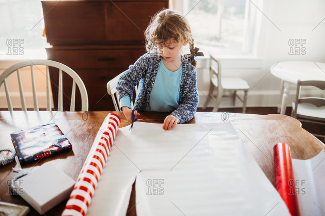 Little girl cutting wrapping paper for Christmas presents