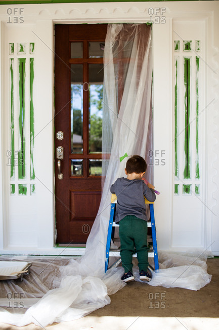 Toddler boy helping with front of house painting project