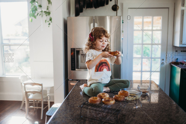Young girl sitting on counter eating homemade donut
