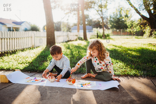 Two young kids decorating small pumpkins