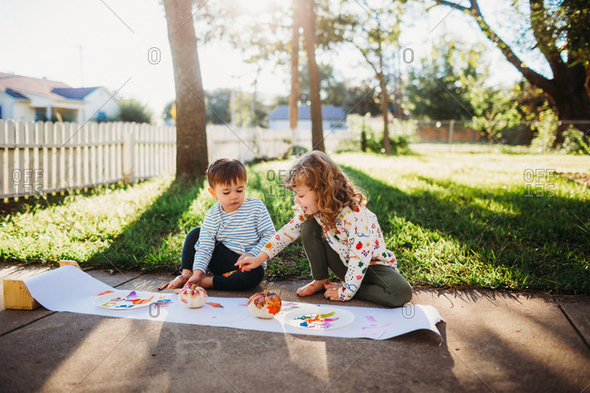 Two young kids painting small pumpkins
