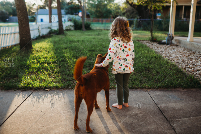 Young girl standing on sidewalk petting her dog