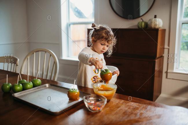 Little girl dipping apple into caramel sauce