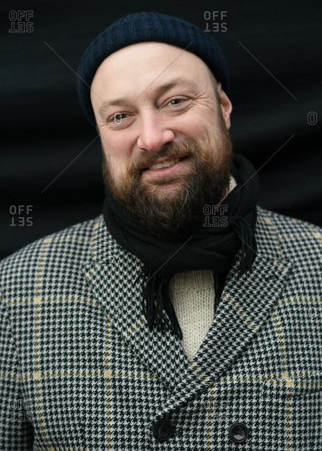 Portrait of a smiling bearded man wearing a knit hat and a scarf
