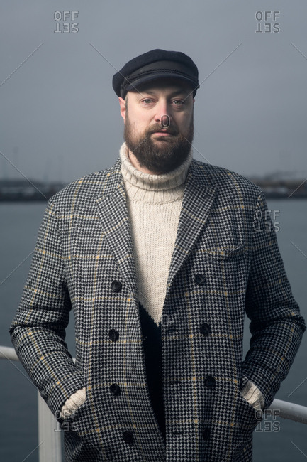 Portrait of a bearded man wearing a wool jacket and a captain's cap standing against the railing of a boat