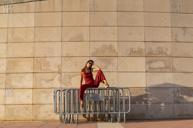Spain- Barcelona- Montjuic- young woman wearing red jumpsuit sitting on barriers