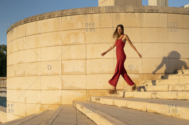 Spain- Barcelona- Montjuic- young woman wearing red jumpsuit walking on stairs