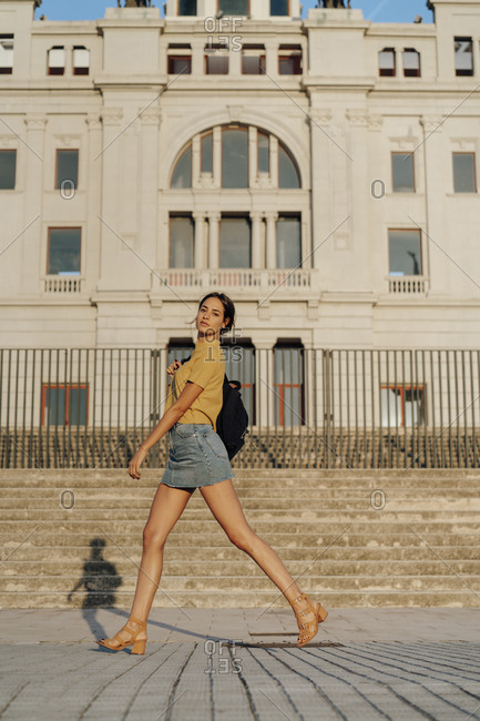 Spain- Barcelona- Montjuic- portrait of young woman passing a building