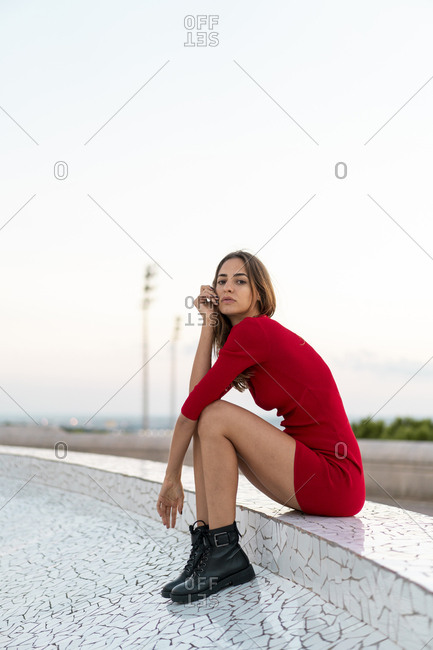 Spain- Barcelona- Montjuic- young woman wearing red dress sitting on a wall