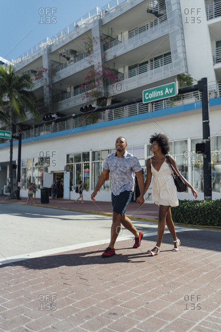 USA- Florida- Miami Beach- happy young couple crossing the street