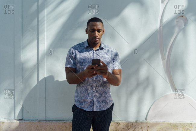 Serious young man wearing shirt looking at cell phone at a wall