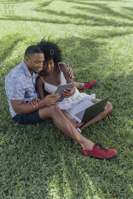Smiling young couple sharing tablet on lawn in a park