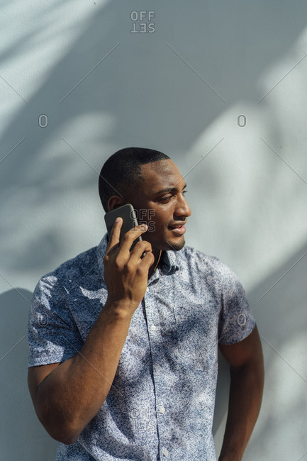 Young man wearing shirt talking on cell phone at a wall