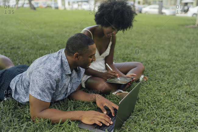 Young couple using tablet and laptop on lawn in a park