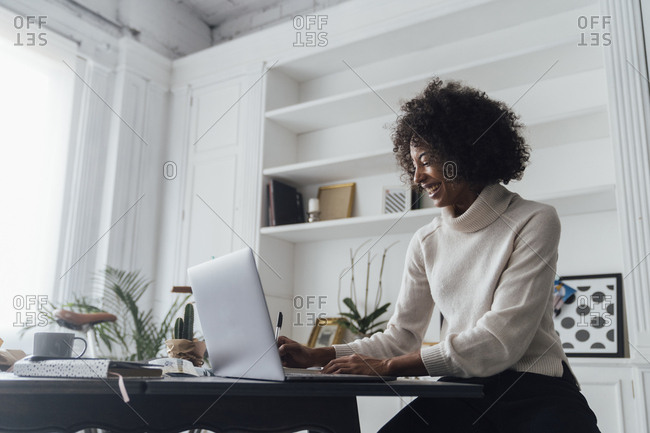 Mid adult woman working in her home office- using laptop