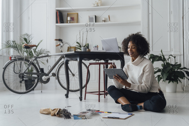 Designer sitting on ground of her home office- using digital tablet