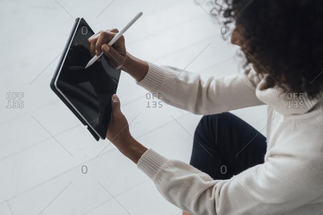Designer sitting on ground of her home office- using digital tablet