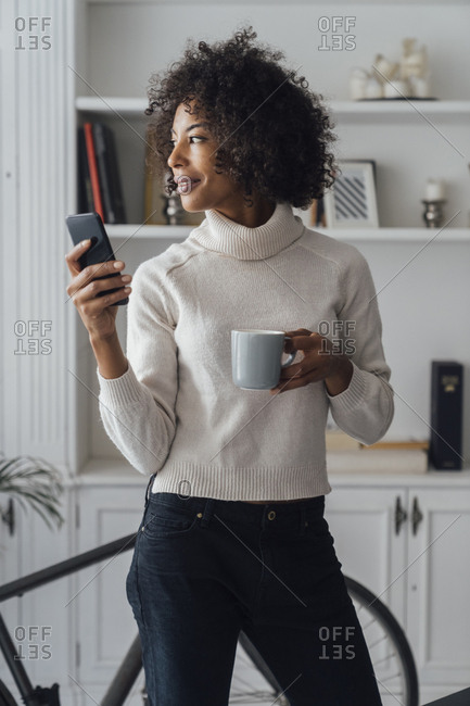 Mid adult freelancer standing in her home office- using smartphone- holding coffee cup
