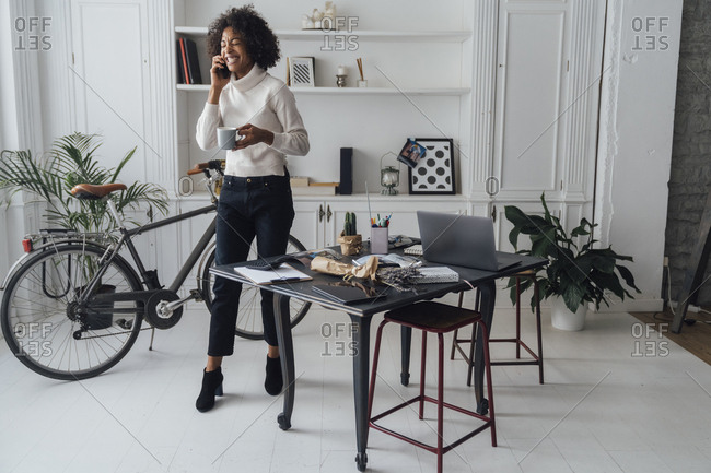 Mid adult freelancer standing in her home office- drinking coffee- talking on the phone