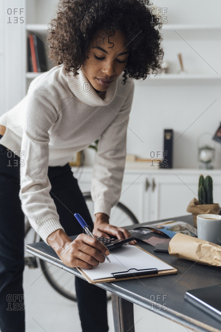 Freelancer standing at her desk- using calculator- taking notes