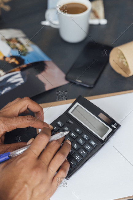Hand of a woman using calculator