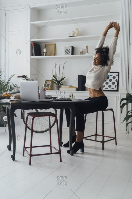 Mid adult woman sitting in her home office- smiling and stretching