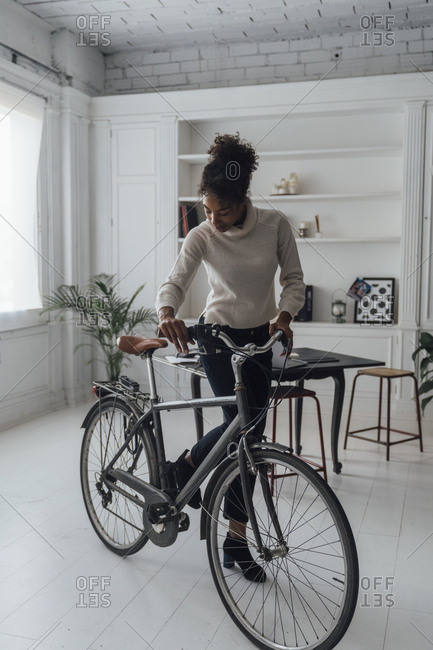 Mid adult woman leaving her home office- pushing bicycle