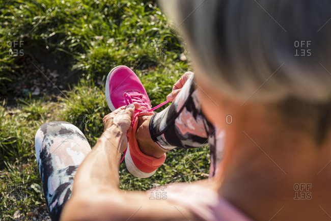 Sportive senior woman tying her shoes