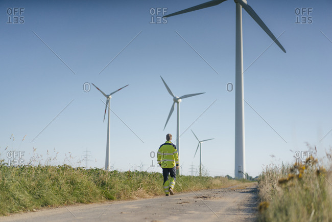 Engineer walking on field path at a wind farm