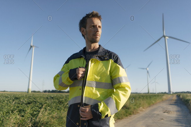 Portrait of an engineer on field path at a wind farm