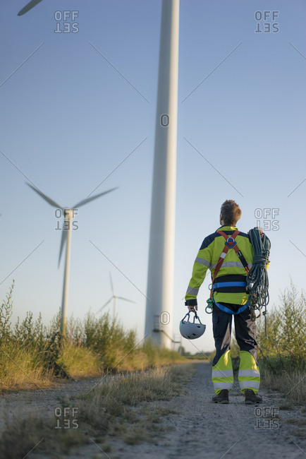 Technician standing on field path at a wind farm with climbing equipment