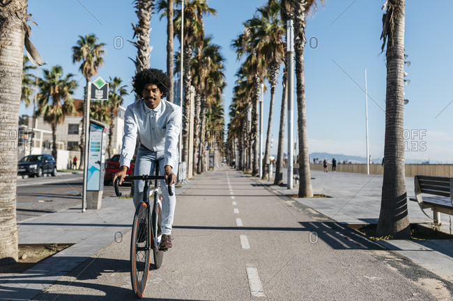Mid adult man riding bicycle in the city- near the beach
