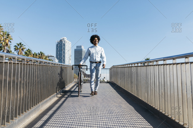 Mid adult man pushing his bicycle on a bridge in the city