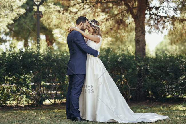 Bridal couple standing head to head with eyes closed in a park