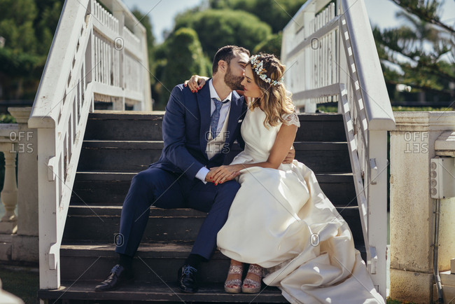Bridal couple sitting on stairs enjoying their wedding day