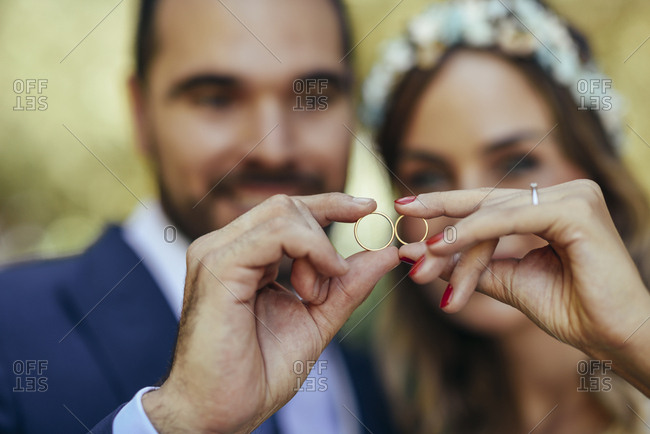 Happy bridal couple showing their wedding rings- close-up