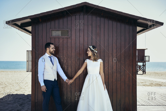 Bridal couple standing hand in hand in front of beach hut looking at each other