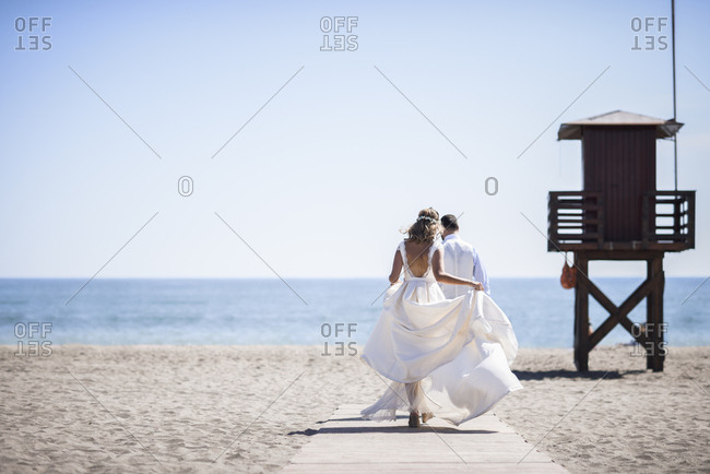 Back view of bridal couple enjoying  wedding day walking on the beach
