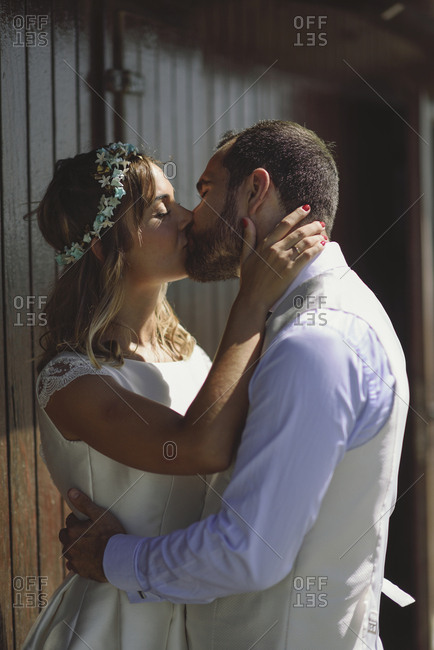 Kissing bridal couple in front of a beach hut
