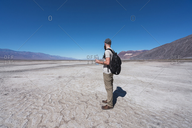 USA- California- Death Valley- man with backpack and water bottle standing in desert looking at distance