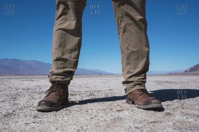 USA- California- Death Valley- man standing in desert- partial view