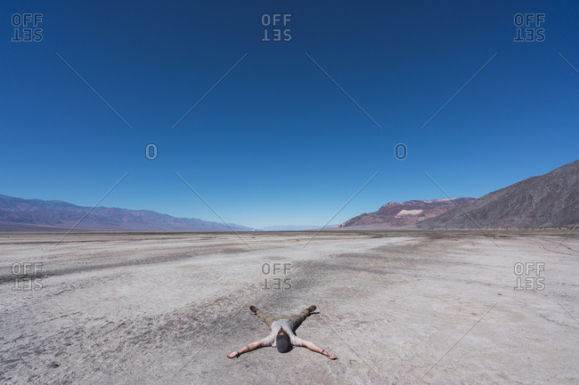 USA- California- Death Valley- man lying on ground in the desert