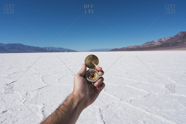 USA- California- Death Valley- man's hand holding compass